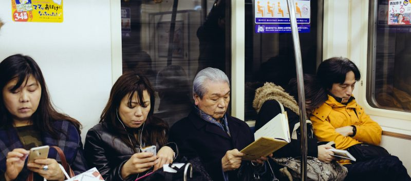 3 generations of women sitting in line on a subway